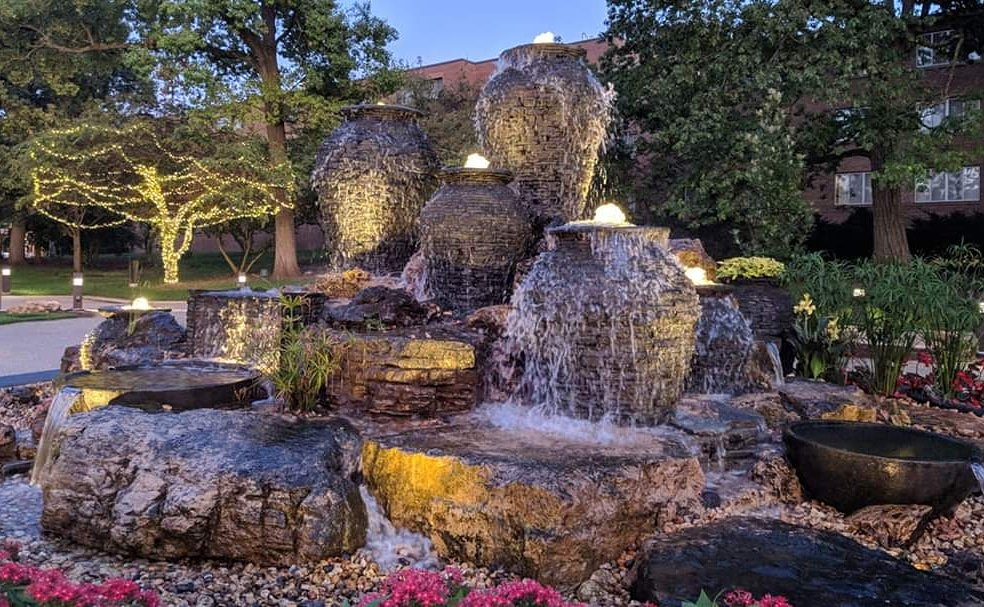 Large collection of fountain water features with lighting at night time