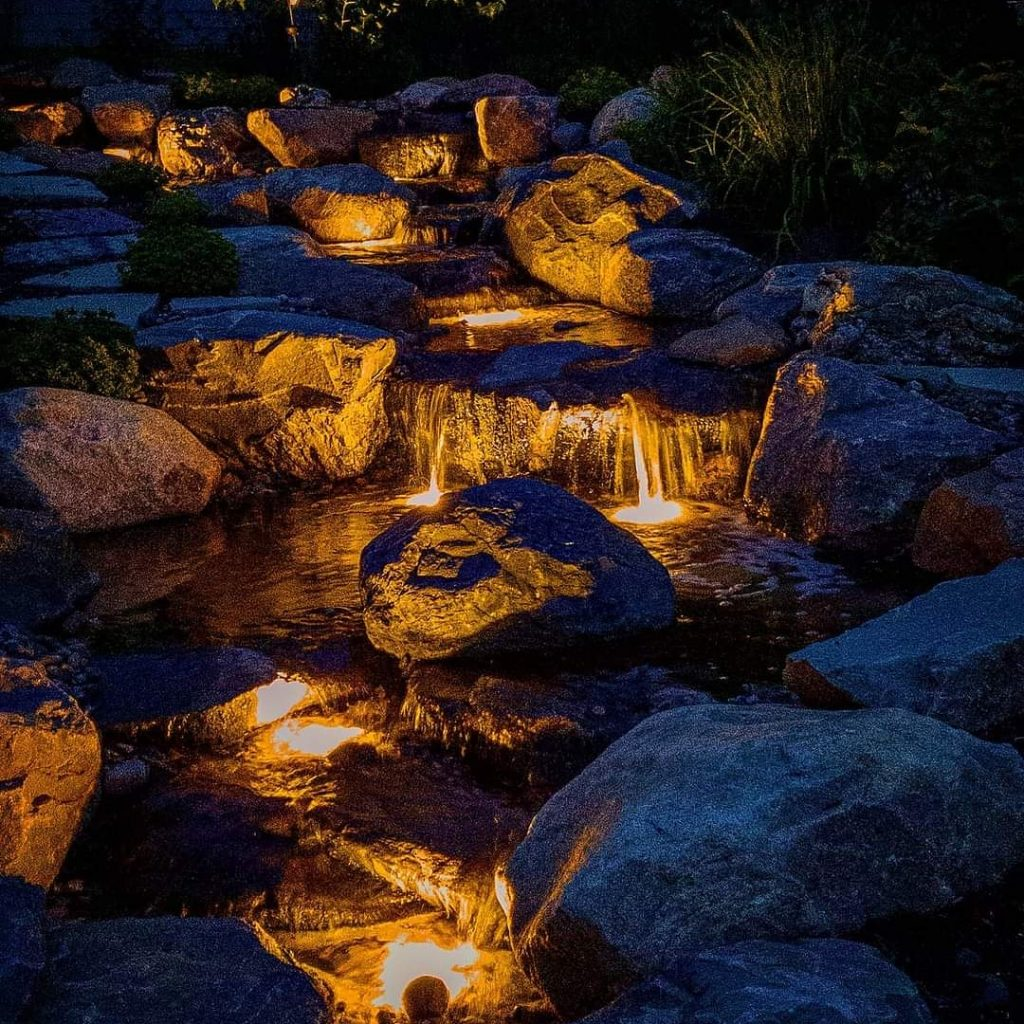 Waterfalls water feature with submerged lighting at night time